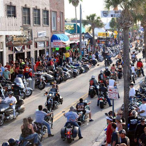 A large group of bikers rides down the street during Daytona Bike Week